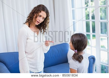 Upset mother looking at her daughter in the living room