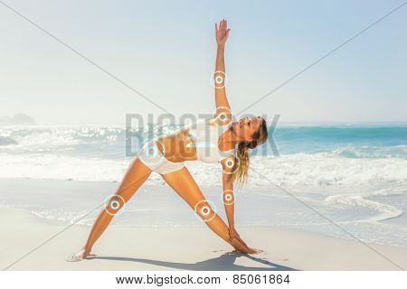 Gorgeous blonde standing in extended triangle pose by the sea against fitness interface