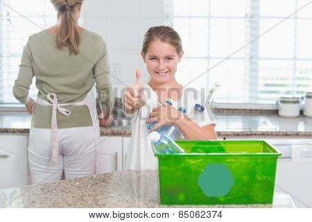 Little girl holding recycling bottles with thumbs up at home in the kitchen