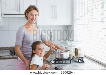 Mother and daughter cooking together at home in kitchen