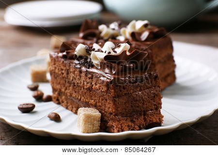 Tasty piece of chocolate cake with lump sugar and coffee beans on wooden table background