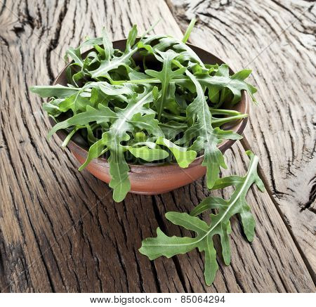 Green arugula leaves in the plate on a wooden table.