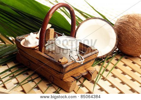 Jar of coconut oil with coconut and leaves on table on light background