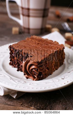 Tasty piece of chocolate with lump sugar and cinnamon sticks cake on wooden table background