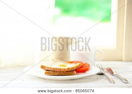 Scrambled egg with bread on plate with cup of tea on bright background