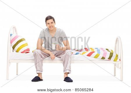 Guy drinking his morning coffee seated on a bed isolated on white background