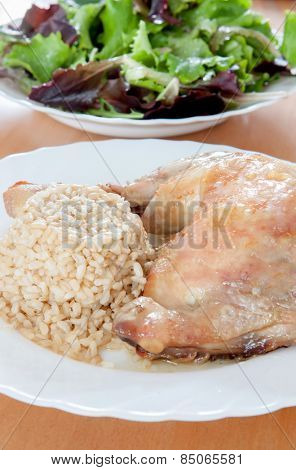 Roasted chicken leg with rice and salad