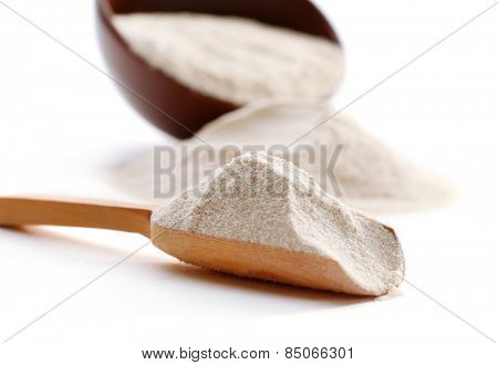 Flour in bowl and wooden spoon isolated on white