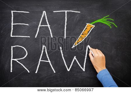 EAT RAW words written on blackboard - new trend in nutrition. The raw food diet consist of eating only uncooked, unprocessed generally vegetables and fruits, often in the form of smoothies and juices.