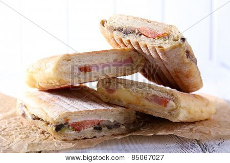 Fresh and tasty sandwiches on paper on wooden background