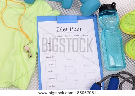 Diet plan and sports equipment top view close-up