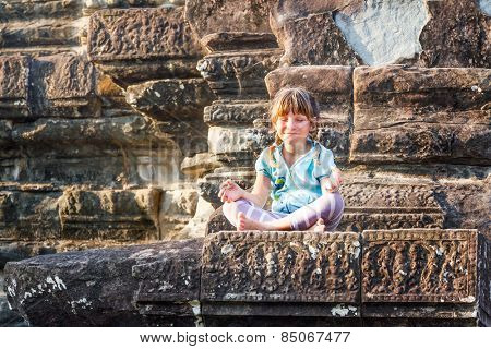 young happy child girl tourist meditating in angkor wat, cambodia