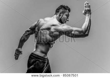Handsome muscular mna posing over gray background. HDR monochrome
