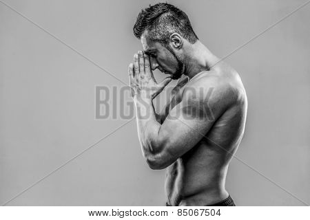Portrait of a young muscular man praying over gray background. HDR monochrome.