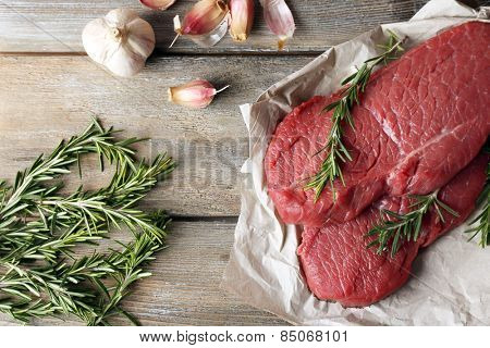 Raw beef steak with rosemary and garlic on paper on wooden background