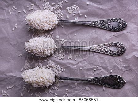 Different kinds of rice in spoons on paper background