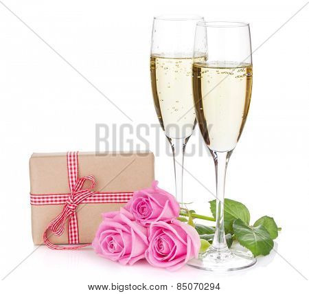 Two champagne glasses, gift box and pink rose flowers. Isolated on white background