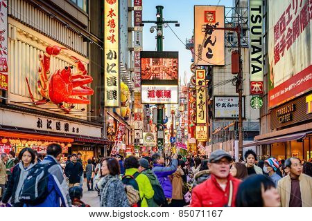 OSAKA, JAPAN - NOVEMBER 25, 2012: Crowds walk below the signs of Dotonbori. With a history reaching back to 1612, the district is now one of Osaka's primary tourist destinations.