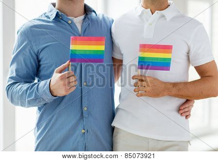 people, homosexuality, same-sex marriage, gay and love concept - close up of happy male gay couple hugging and holding rainbow flags at home