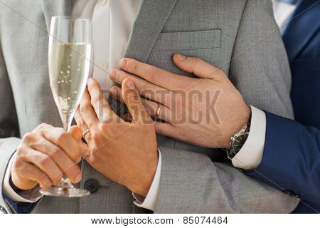 people, celebration, homosexuality, same-sex marriage and love concept - close up of happy married male gay couple in suits drinking sparkling wine from glass on wedding