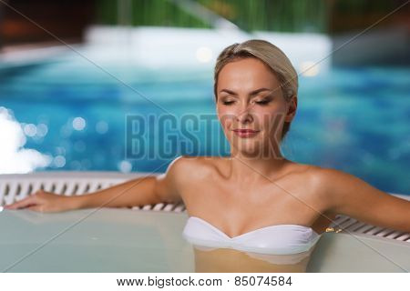 people, beauty, spa, healthy lifestyle and relaxation concept - beautiful young woman wearing bikini swimsuit sitting in jacuzzi at poolside
