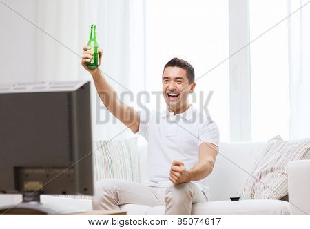 home, people, technology and entertainment concept - smiling man with remote control watching tv and drinking beer at home