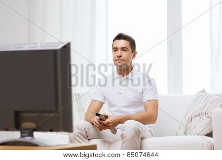 home, people, technology and entertainment concept - man with remote control watching tv at home