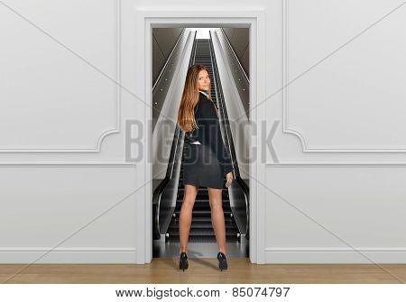 Business woman standing in the doorway going on escalator