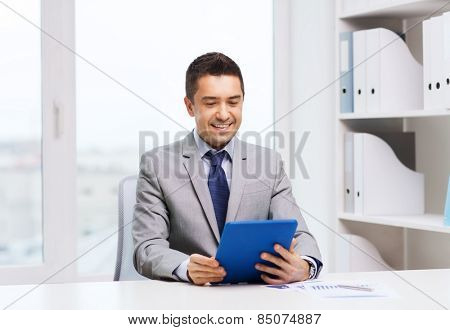 business, education, people and technology concept - smiling businessman with tablet pc computer in office