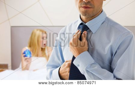 people, business, morning and work concept - close up of man in shirt dressing up and adjusting tie on neck over bedroom with woman holding alarm clock background