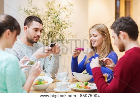 people, leisure, friendship and technology concept - group of happy friends with smartphones taking picture of food at cafe
