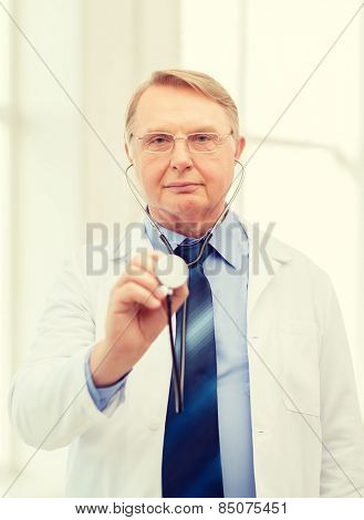 healthcare and medicine concept - calm standing doctor in eyeglasses or professor in eyeglasses with stethoscope