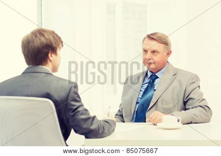 business, technology and office concept - older man and young man signing papers in office