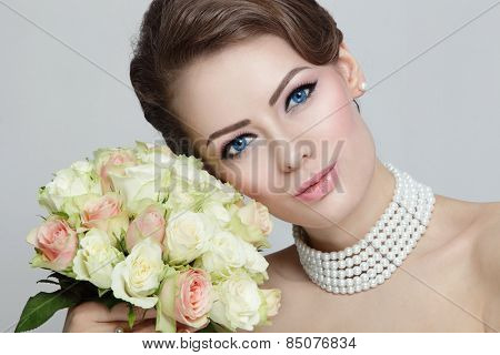 Close-up portrait of young beautiful bride with stylish make-up and hairdo holding bouquet