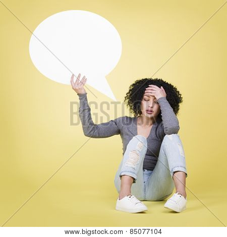 Unhappy woman being depressed  holding a white blank paper sign board with empty copy space, isolated on yellow background.