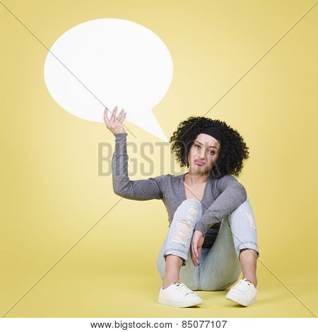 Irritated woman being unhappy holding a white blank paper speech bubble with empty copy space, isolated on yellow background.