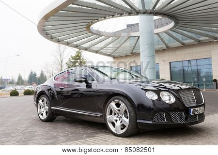 WARSAW, POLAND - 28 FEBRUARY 2014: Bentley Continental GT parked at the DoubleTree by Hilton Hotel & Conference Centre in Warsaw, Poland. Hilton has over 400 hotels and resorts around the world.
