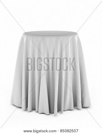 Round presentation pedestal covered with a white cloth over white background