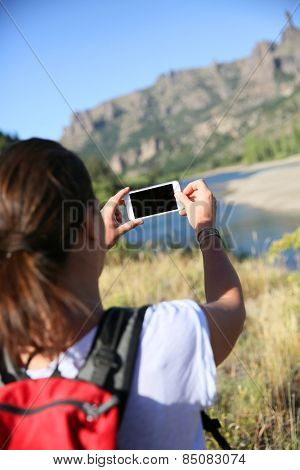 Backpacker taking picture of Limay river, Patagonia