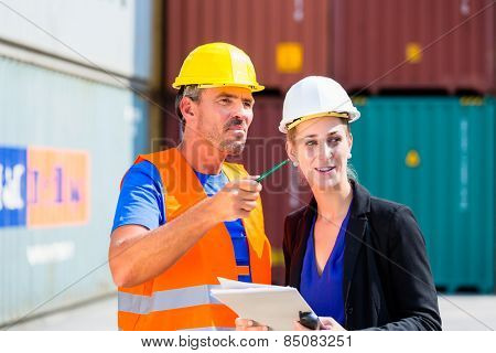 Employees in logistics company shipping containers with clipboard