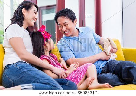Chinese Family playing with daughter on sofa holding stuffed animal