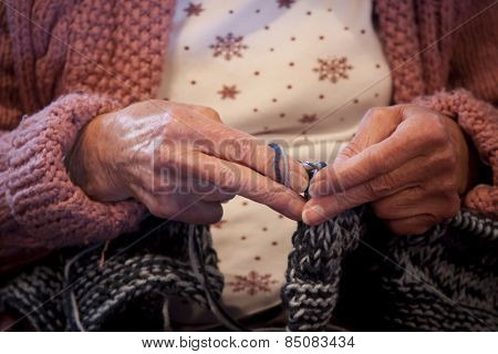 A close up of an elderly woman's hands knitting with blue yarn.