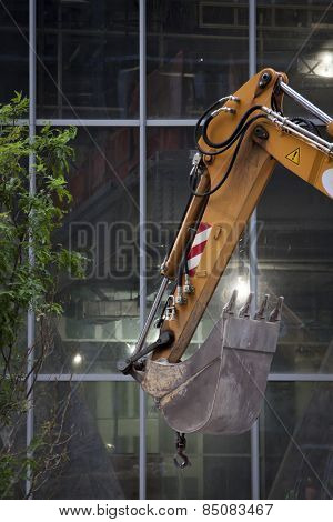 The steel bucket of a hydraulic excavator in front of windows of an office building under construction.