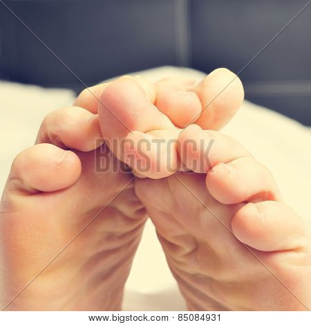 closeup of a young man rubbing his bare feet together in bed