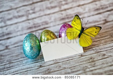 Small Blank Greeting Card with Yellow Green Butterfly on Upper Right Corner and Colored Easter Eggs Behind, Placed on Top of a Rustic Table with blurry Background.