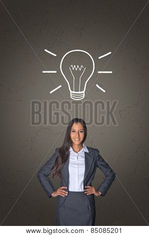 Innovative young businesswoman with a vision and bright idea standing below a shining light bulb drawn on a chalkboard