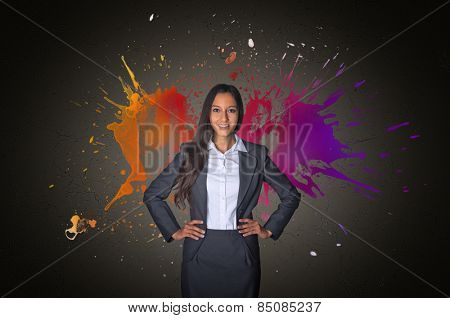 Artistic colorful portrait of a smiling attractive young Asian businesswoman standing with her hands on her hips below two vivid splashes of color in the shades of orange, purple and magenta
