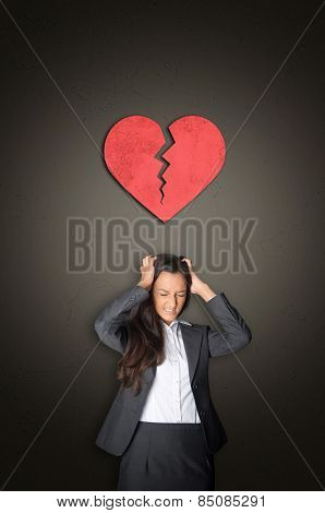 Young Businesswoman in Despair Tearing her Hair with Conceptual Red Broken Heart Above her on Abstract Gray Gradient Background.