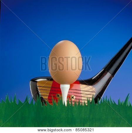 Golf club hitting an egg like golf ball.Funny golf concept.