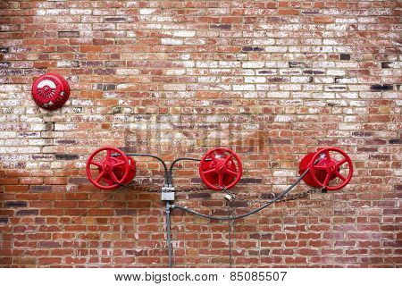 Red Sprinkler Valves against Red Brick Background
